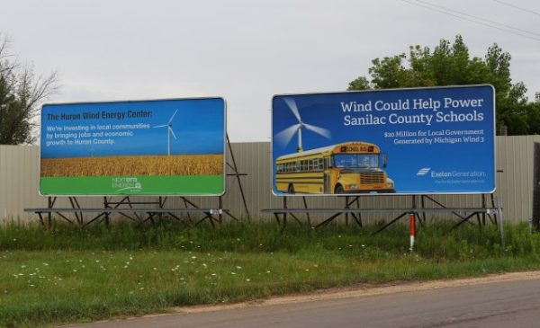 Signs promoting the economic benefits of wind turbine projects like these at the intersection of M-81/M-53 are popping up throughout Michigan's Thumb region. At the same time, wind companies are taking local jurisdictions to court over claims of paying too much in taxes. (Photo by John Cook)
