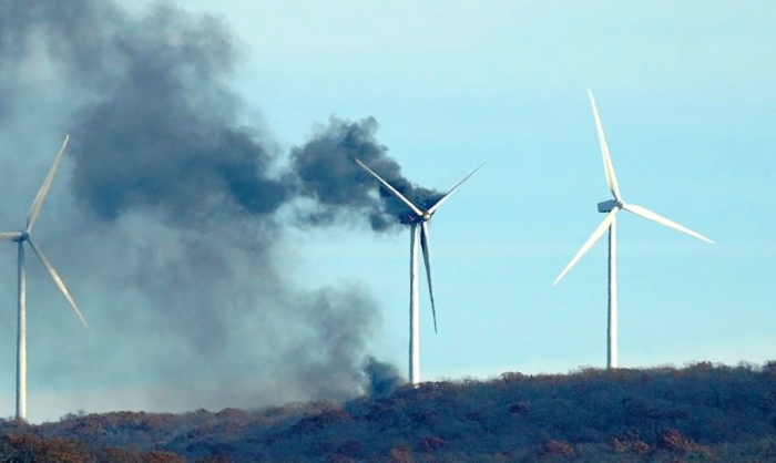 MARK MORAN / THE CITIZENS' VOICE. A windmill smolders Thursday on Bald Mountain in Bear Creek Township.